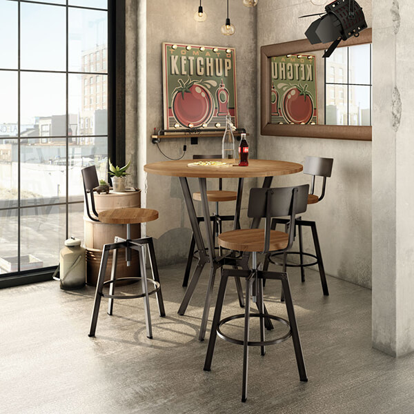 A metal and wood round pub table with four industrial style bar stools near a window