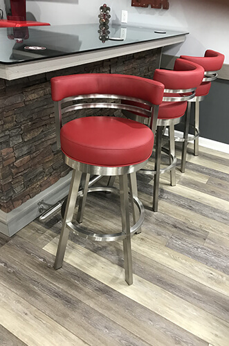 Wesley Allen's Miramar Modern Swivel Barstools in Stainless Steel and Red Vinyl - Shown in Modern Basement Bar