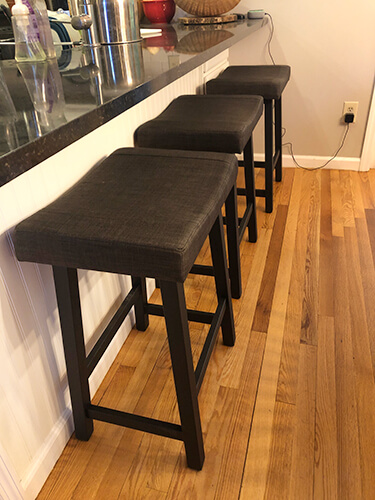 Amisco's Miller Backless Saddle Counter Stool in Black Metal Finish Shown in Transitional Kitchen with Hardwood Flooring