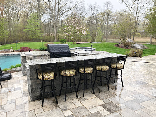 Lisa Furniture's Outdoor Swivel Barstools in Black Metal Finish with Arms and Seat Cushion - Shown Outside Kitchen Grill Area with Pool