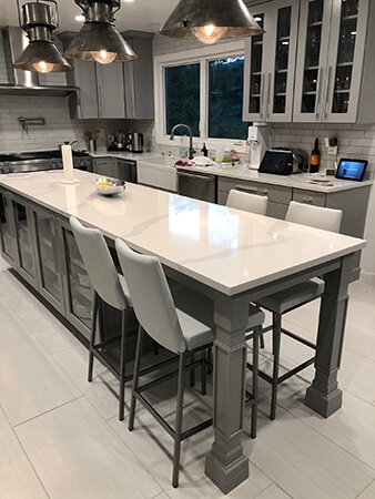 Amisco's Linea Upholstered Bar Stools with Back in Silver Metal Finish and Gray Upholstery - Shown in Transitional Gray Kitchen