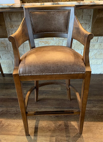 Fairfield's Gilroy Upholstered Wooden Brown Bar Stool with Arms and Nailhead Trim