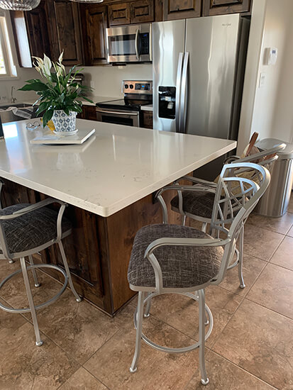 Wesley Allen's Boston Swivel Counter Stools with Arms in Nickel Metal Finish with Gray Seat Cushion in Modern Kitchen