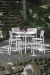 Woodard's New Century Iron Bar Stools Near Table, Shown in Hammered White