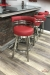 Wesley Allen's Miramar Swivel Barstools in Stainless Steel with Round Curved Back and Seat in Red Vinyl - Shown in Modern Basement Bar