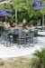 Woodard's Canaveral Harper Woven Outdoor Counter Stools on Patio with Table Near Pool