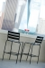 Woodard's Cafe Series Metro Outdoor Black Bar Stools with Ladder Back Design Outside on Deck with Martini Glasses
